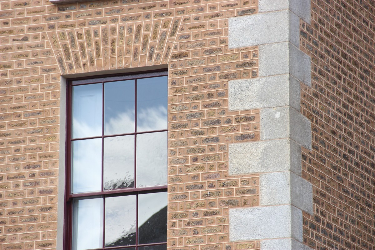 Crisply pointed brickwork and granite quoins