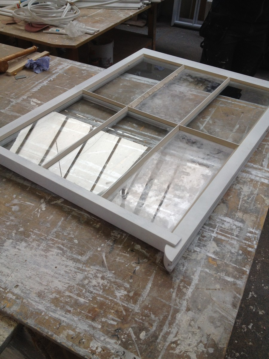 New sash window with fresh putty, destined for the rear elevation.